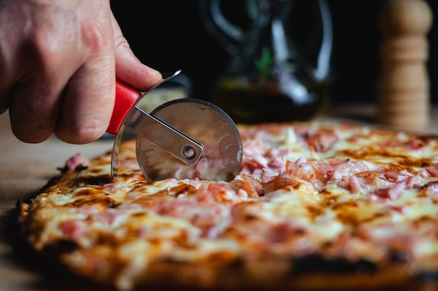 Un uomo che taglia una pizza usando un tagliapizza. ci sono origano, olio d'oliva e pepe in sottofondo. (orizzontale)
