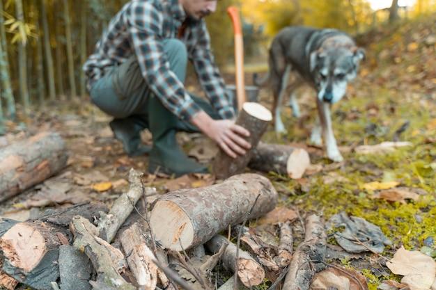 Uomo che taglia con un'ascia con il suo cane polvere e movimenti amante degli animali