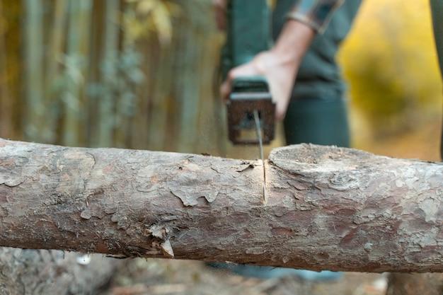 Uomo che taglia con sega elettrica polvere e movimenti taglialegna seghe albero con motosega su segheria