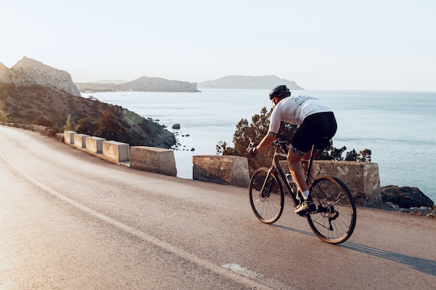 Uomo ciclista pedalando su una bici da strada all'aperto nel tramonto