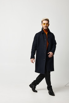 Un uomo con un cappotto scuro e pantaloni cammina di lato su uno sfondo chiaro tendenza del modello di stagione