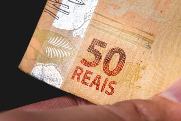 Uomo in un luogo buio con in mano una banconota da 50 reais in real brasiliano