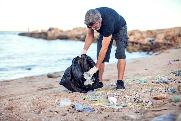 Uomo in camicia scura e pantaloncini con guanti bianchi e grande pacchetto nero che raccoglie immondizia sulla spiaggia. protezione ambientale e concetto di inquinamento del pianeta