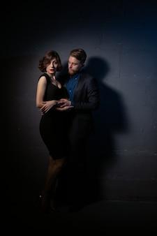 Un uomo a un muro scuro abbraccia dolcemente la sua amata donna