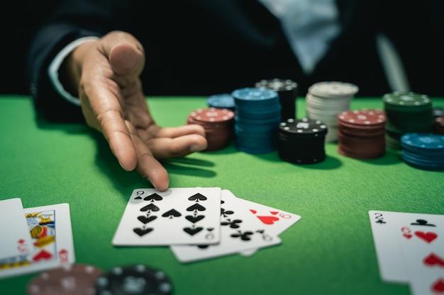 L'uomo commerciante o croupier mescola le carte da poker in un casinò