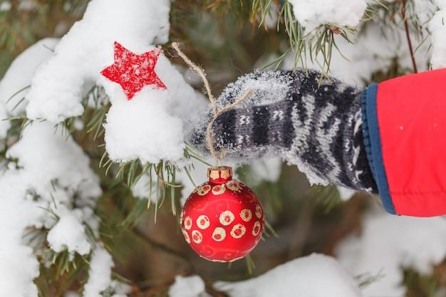 L'uomo decora un albero di pelliccia in legno d'inverno