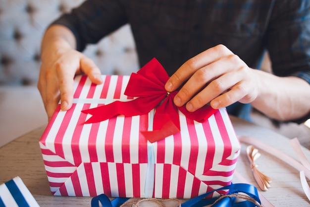 Uomo che decora confezione regalo con fiocco rosso.