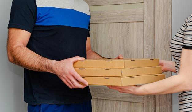 Uomo che consegna la pizza a casa di un cliente. concetto di ordine alimentare.