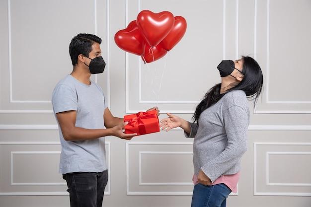 Uomo che consegna il regalo di san valentino, indossa una maschera per il viso, nuova normalità