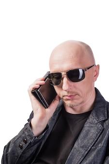 Uomo in giacca di jeans e occhiali da sole che parla al cellulare