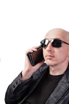 Un uomo con una giacca di jeans e occhiali da sole che parla al cellulare