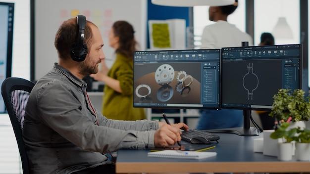 Architetto designer uomo che lavora al nuovo progetto utilizzando un pc con software grafico graphic