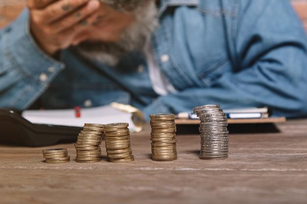 Uomo alla scrivania in camicia di jeans che tiene la testa e preoccuparsi per i soldi.