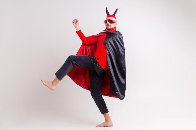Uomo nella posa del costume di travestimento del diavolo.