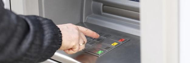 L'uomo compone il codice pin per prelevare denaro dal bancomat. l'uomo si trova vicino al terminal per prelevare denaro. pagamento di beni e servizi tramite bancomat. inserimento sicuro della password per prelievi di contanti