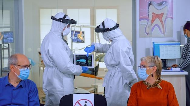 Uomo che discute con l'infermiera nella reception dentale che indossa una tuta protettiva contro il coronavirus, pazienti anziani in attesa alla reception mantenendo le distanze. concetto di nuova normale visita dal dentista nello scoppio.