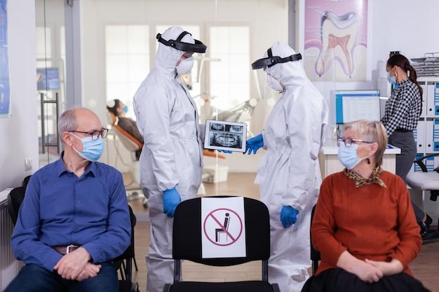 Uomo che discute con l'infermiera nella reception dentale indossando tuta protettiva contro il coronavirus, pazienti anziani in attesa alla reception mantenendo le distanze