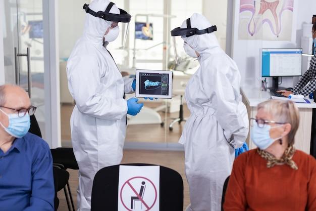 Uomo che discute con l'infermiera nella reception odontoiatrica che indossa tuta protettiva
