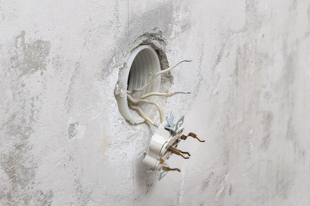 Un uomo smonta e ripara la presa elettrica per le riparazioni. presa di alimentazione.