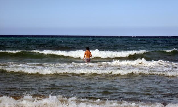L'uomo si tuffa nelle onde del mare