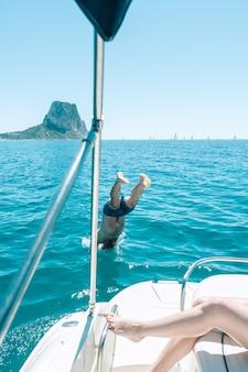 Uomo che si tuffa in acqua dalla barca