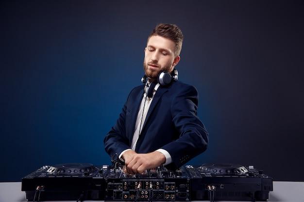 Uomo dj in abito scuro suona musica su uno studio di mixer dj girato spazio blu scuro