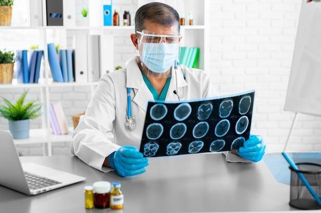Uomo medico esaminando la risonanza magnetica mentre è seduto al tavolo in ospedale