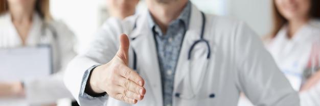 Medico dell'uomo che mostra pollice in su sullo sfondo dei colleghi in clinica