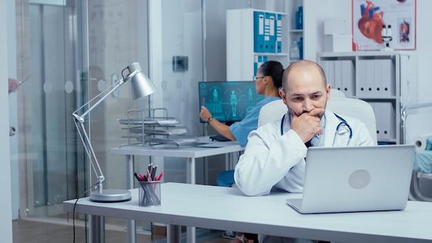Medico dell'uomo che digita sul computer portatile in un ufficio moderno con pareti di vetro, personale medico e pazienti che camminano nel corridoio. consultazione clinica del sistema sanitario da parte di un medico professionista. scatto a mano libera