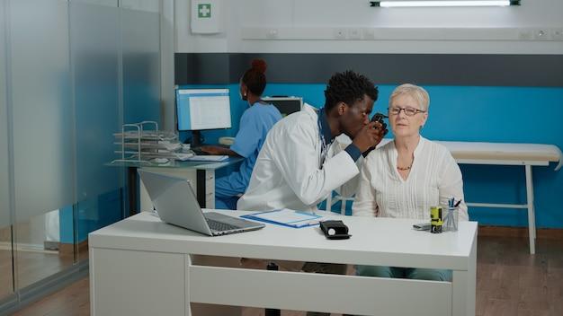 Medico dell'uomo che utilizza l'otoscopio per l'esame dell'orecchio