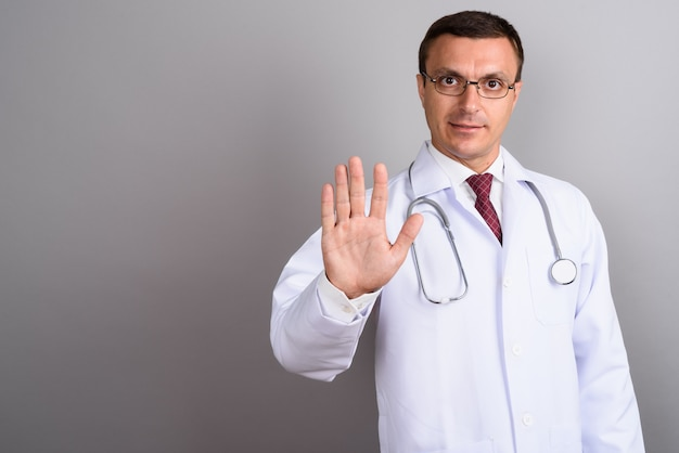 Equipaggi gli occhiali da portare del medico contro la parete grigia
