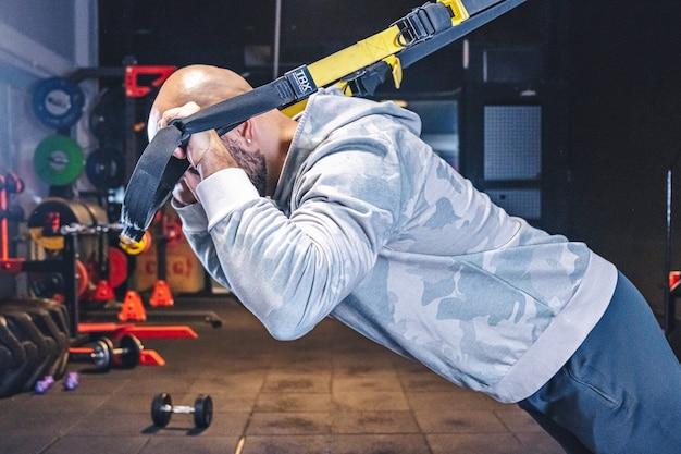 L'uomo fa esercizi di crossfit con cinghie di fitness trx in palestra