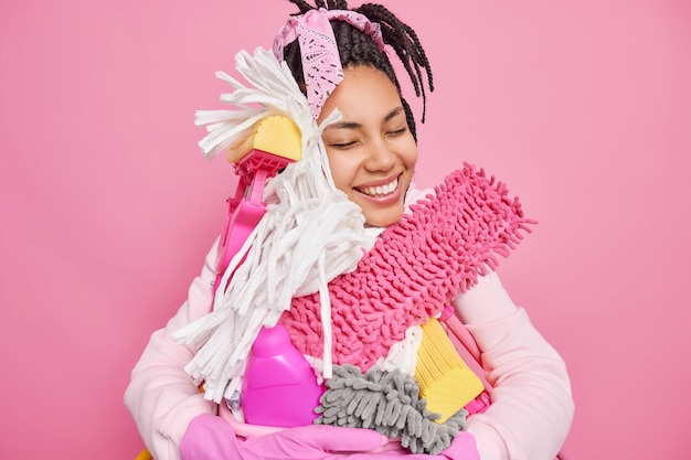 L'uomo fa le faccende domestiche abbraccia gli strumenti per la pulizia e la bacinella del bucato si diverte con i lavori domestici sorride felicemente isolato sul rosa