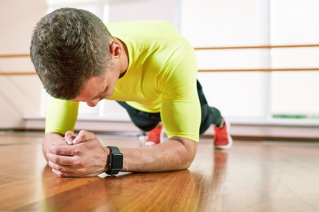 L'uomo fa un esercizio di plancia nel corridoio sul pavimento di fronte alla finestra. stile di vita sportivo, vita in movimento.