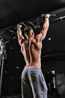 Un uomo fa pull-up sulla palestra della barra orizzontale, motivazione per il fitness