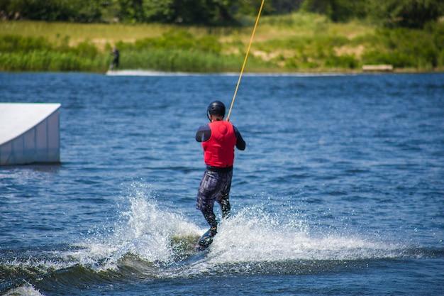 L'uomo fa wakeboard sull'acqua in estate con indosso un casco e una muta.