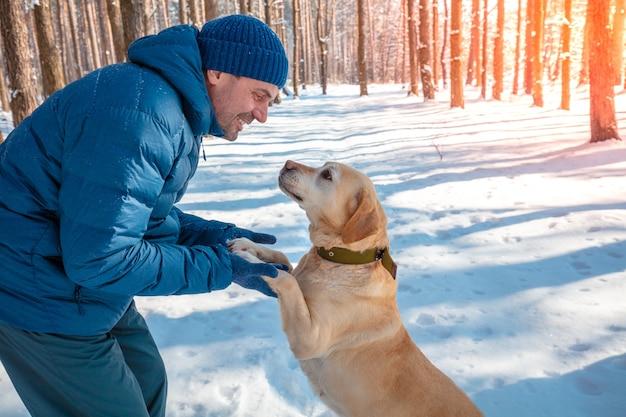 L'uomo e il cane sono i migliori amici. l'uomo gioca con un cane in una foresta innevata in una giornata di sole invernale