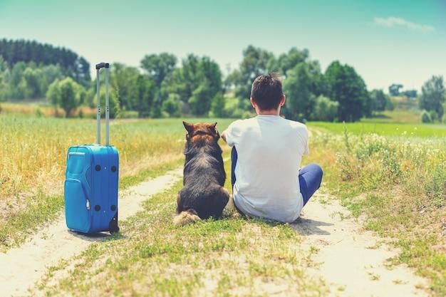 L'uomo e il cane sono i migliori amici viaggiatori. l'uomo e il cane si siede insieme alla valigia di viaggio su una strada sterrata nel campo