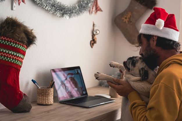L'uomo e il cane si godono la chiamata del laptop con la donna durante le vacanze di natale