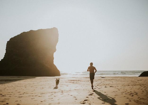 Uomo e cane che corrono sulla spiaggia
