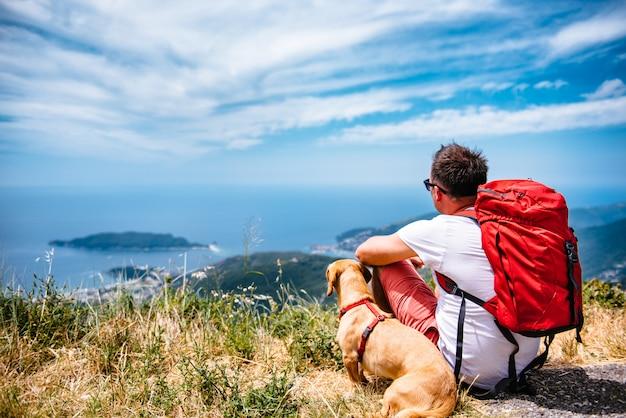 Uomo e cane seduto su una montagna e guardando il mare