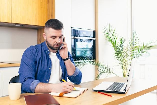 Uomo che fa affari rimanendo a casa seduto in cucina al tavolo e utilizzando un computer portatile