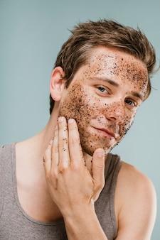 Uomo che fa uno scrub al viso