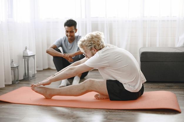 Uomo che fa esercizio di fitness a casa con l'allenatore o un amico. corpo in forma.