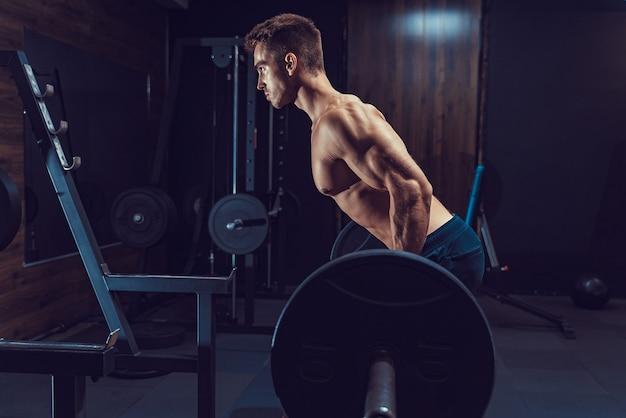 Uomo che fa esercizio pesante per la schiena. ogni cosa ha un prezzo.