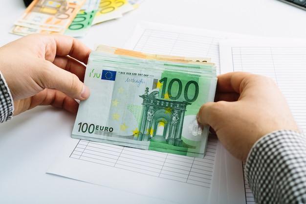 Uomo che fa la sua contabilità con il concetto di attività bancarie in euro