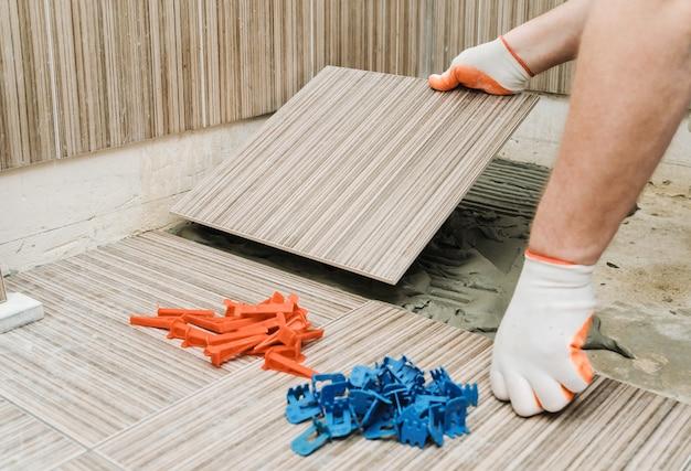 Uomo che fa l'installazione di piastrelle in ceramica.