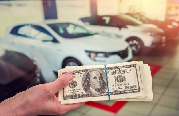 Uomo che acquista o noleggia un'auto dando un venditore di dollari