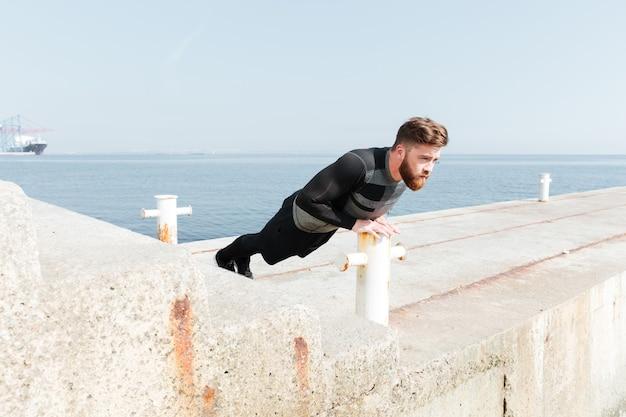 Uomo che fa flessioni vicino al mare. vista laterale