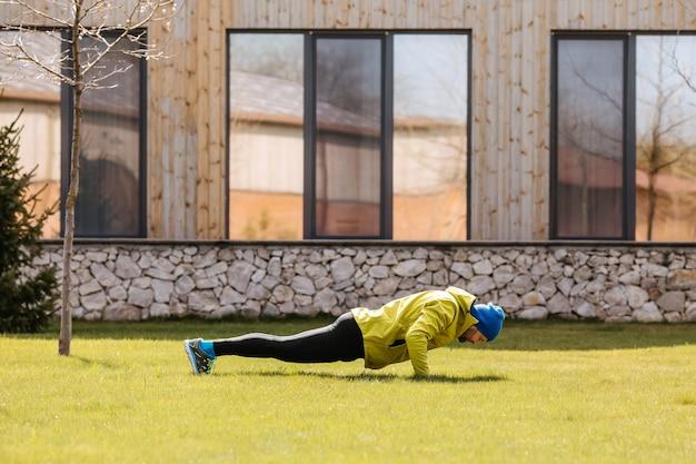 Uomo che fa push up all'aperto sull'erba verde uomo attivo che lavora la mattina nel cortile di casa